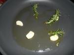 Pfanne mit Olivenöl, Knoblauch und Rosmarin